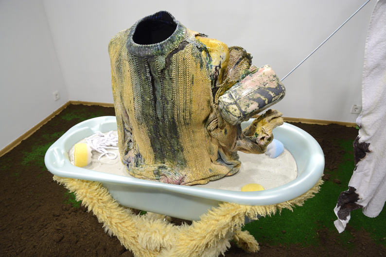 2014. Ceramics, water, plastic, concrete, lamb fur, bathtub, earth, grass imitation, bloody towel, coins, sponges, radio playing live.
